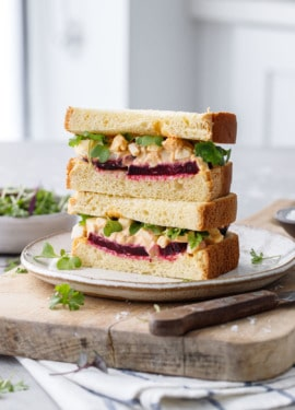 Egg salad sandwich cut in half, showing the layers of beet and egg