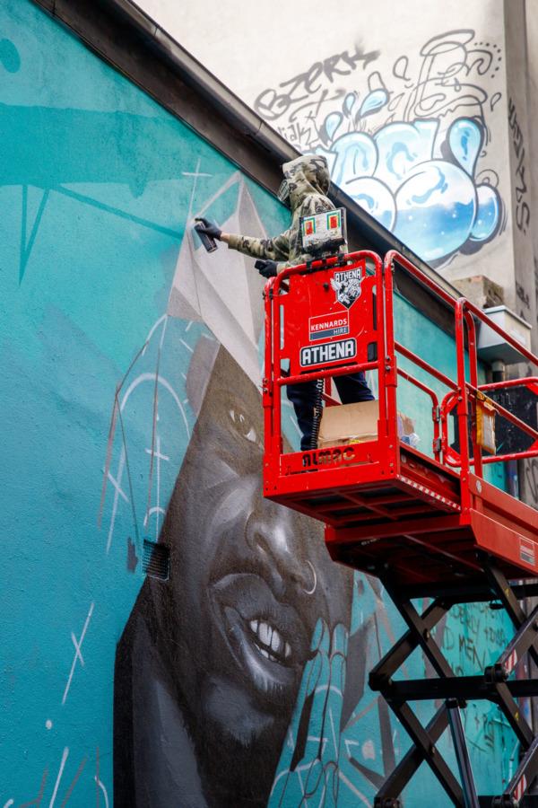 Graffiti artist in a red lift creating art, Hoosier Lane, Melbourne, Australia