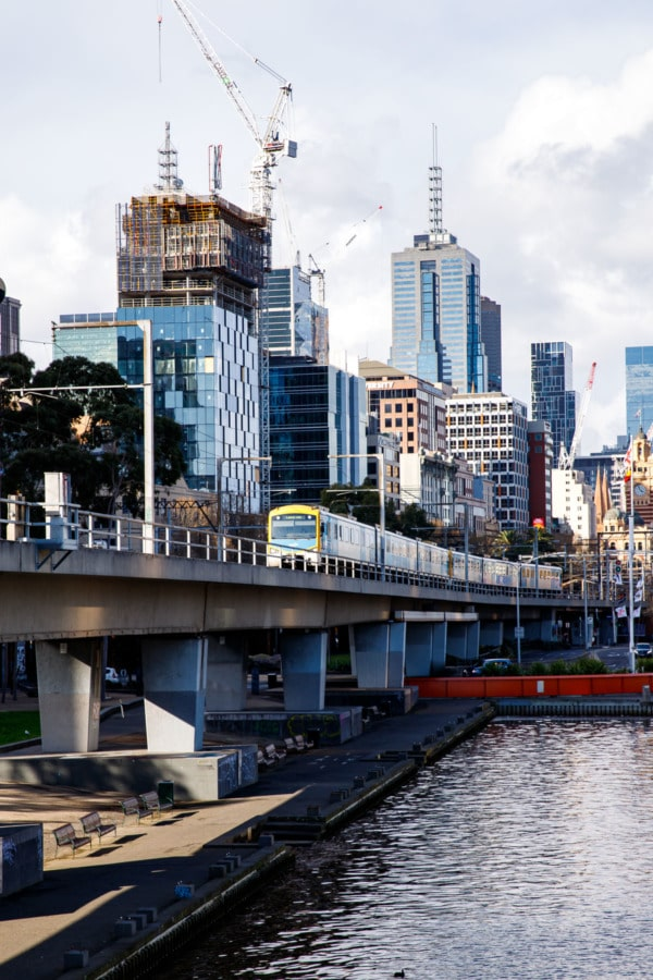 Riverfront, Melbourne, Australia, with yellow tram and buildings.
