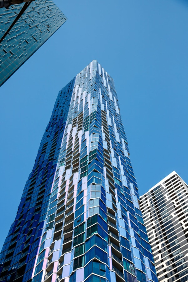 Looking up at a blue glass building with blue sky in Melbourne, Australia