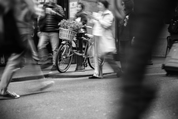 Bike with flower basket, blurred people in motion, black and white.