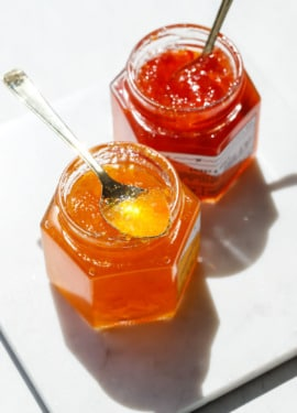 Bright sunlight making the red and orange pepper jelly sparkle