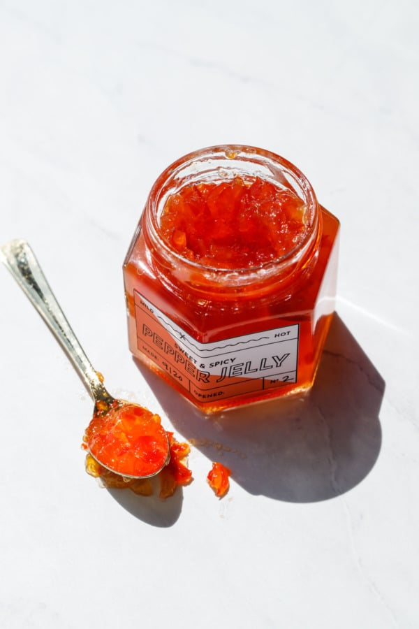 Harsh sunlight jar of red pepper jelly and a gold spoon
