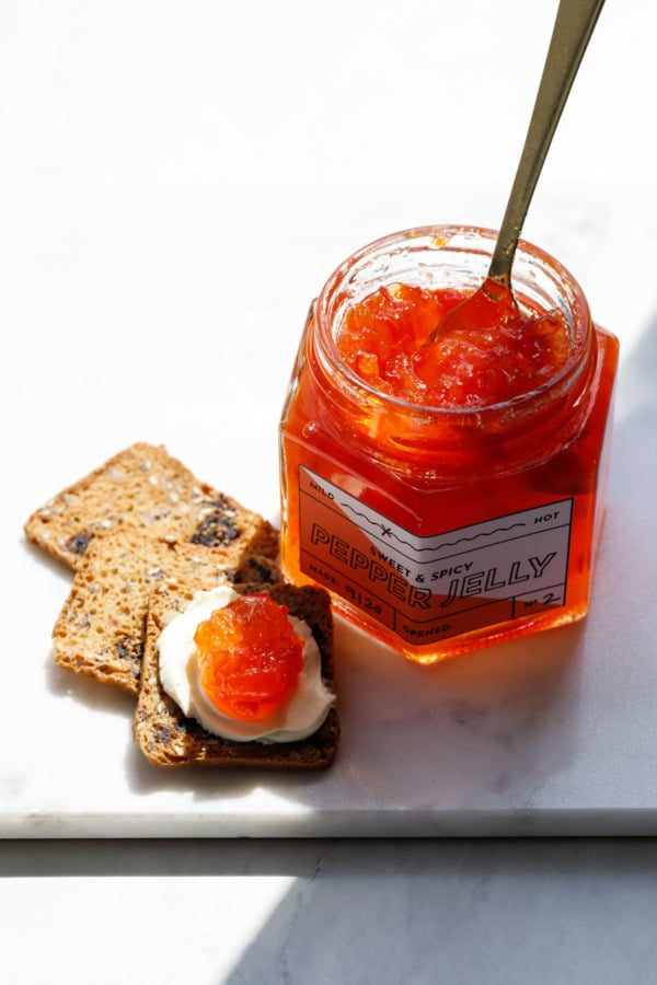 Jar of red pepper jelly with crackers and cream cheese