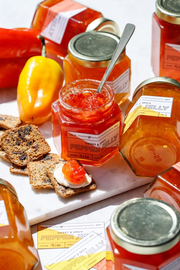 Assorted jars of orange and red pepper jelly with crackers and cream cheese