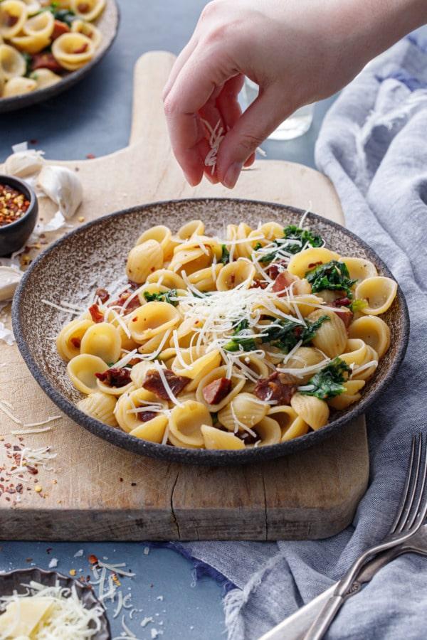 Sprinkling a bowl of orecchiette with pecorino cheese