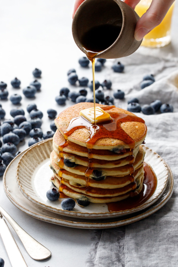 Drizzling maple syrup on a tall stack of blueberry pancakes