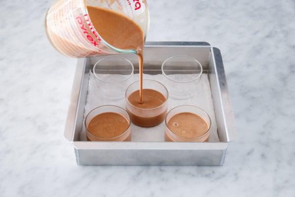 Pouring the creme custard base into glass ramekins, set inside a cake pan