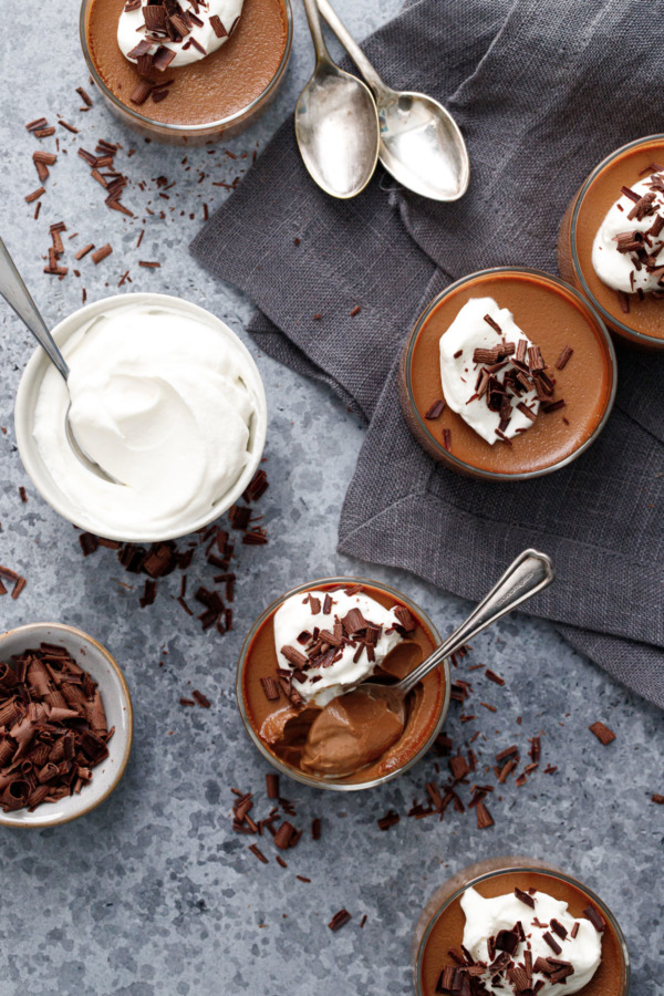 Overhead, Chocolate Pumpkin Pot de Creme with whipped cream and shaved chocolate on a gray background