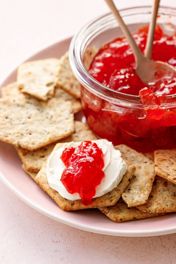 Plate of seeded crackers and a jar of cranberry pepper jelly, one cracker spread with cream cheese and a dollop of jelly
