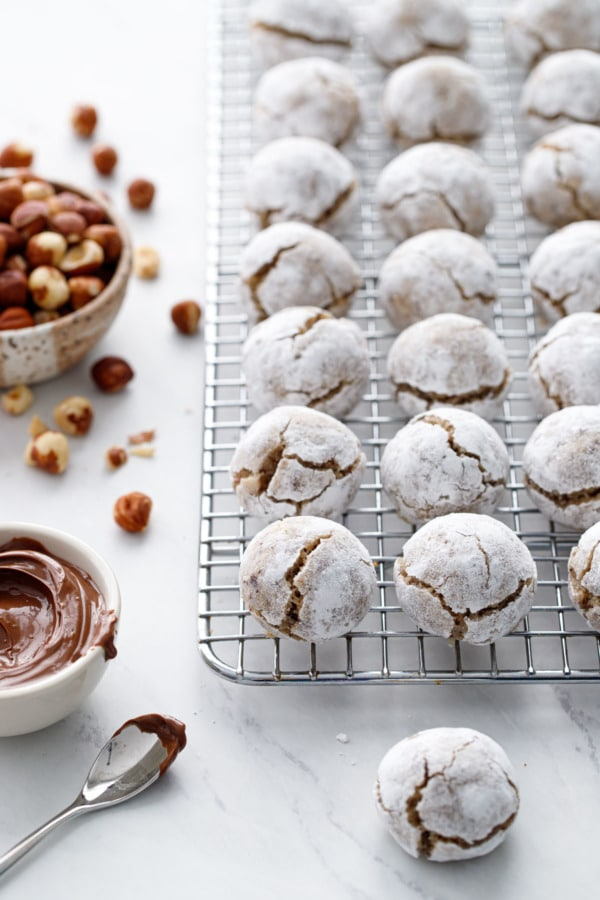 Stuffed Hazelnut Amaretti Cookies on a wire rack, bowl of hazelnuts and nutella on the side