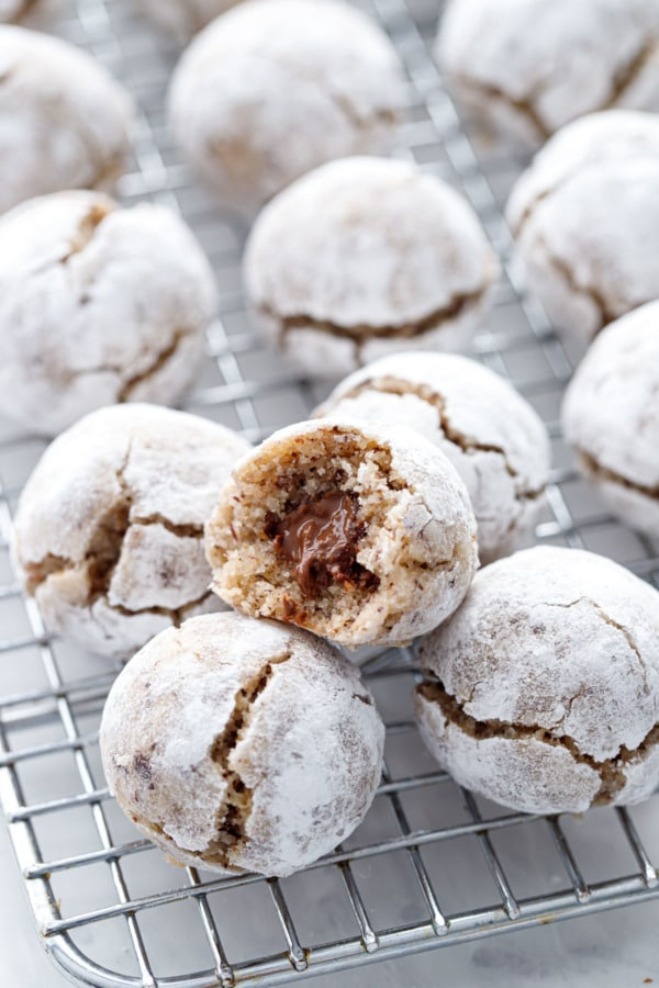 Stuffed Hazelnut Amaretti Cookies on a wire rack, one cookie with a bite out of it showing the Nutella filling inside