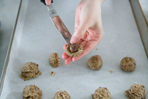Placing a ball of frozen nutella on flattened half of cookie dough