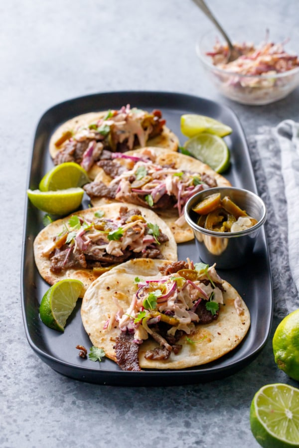 Four steak street tacos on a black rectangular plate, with limes, pickled jalapenos and chipotle slaw