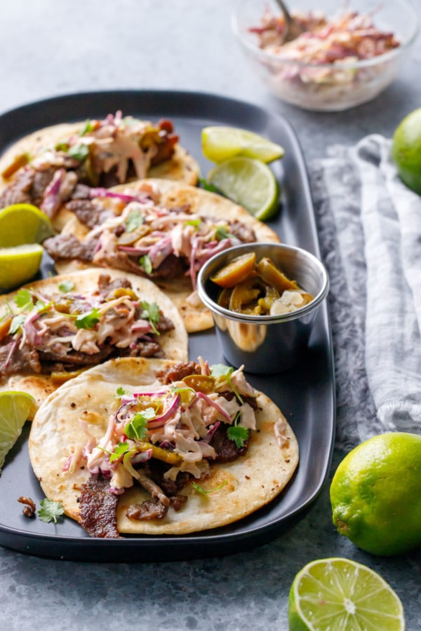 Four flat tacos with steak, slaw and cilantro, slices of limes on the side