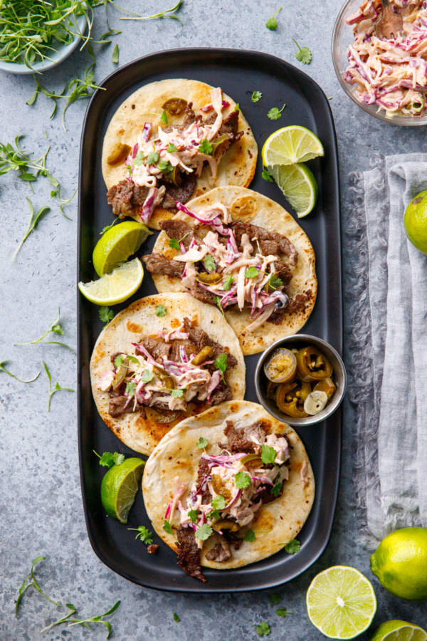 Overhead rectangular black plate with four street tacos with browned tortillas, slices of lime and bowls on the side