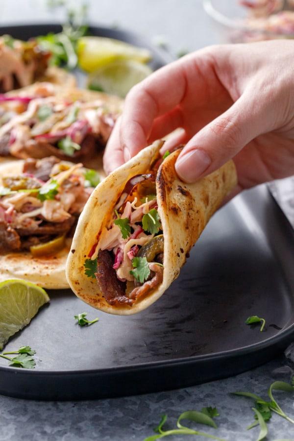Hand lifting a steak street taco off of a black platter