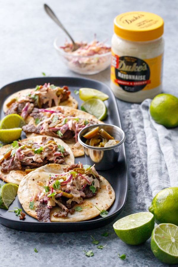 Platter of steak street tacos with jar of Duke's mayonnaise in the background