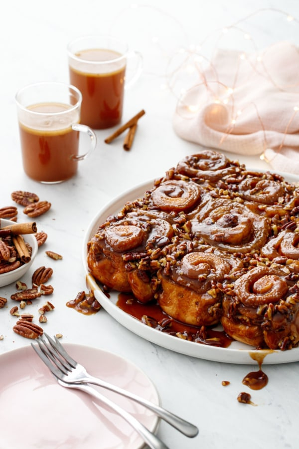Platter of gooey sticky buns with pecans, cups of hot buttered rum in the background