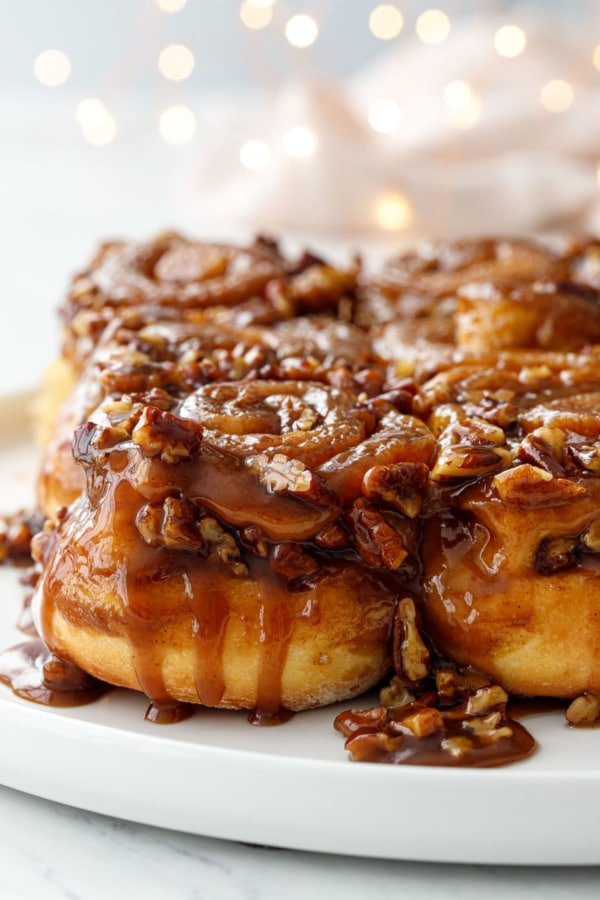 Gooey caramel dripping down the side of hot buttered rum sticky buns, with twinkle lights in the background