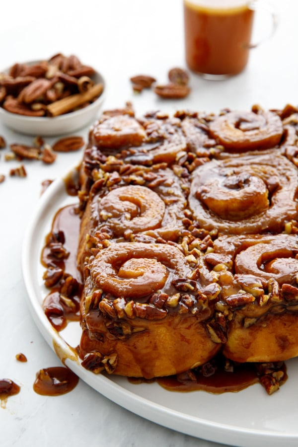 Platter of gooey sticky buns with dish of pecans and a cup of hot buttered rum in the background