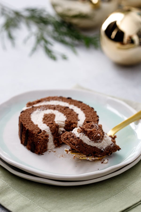 Slice and forkful of Chocolate Chestnut Christmas Cake Roll, showing the light and fluffy texture and chestnut cream filling