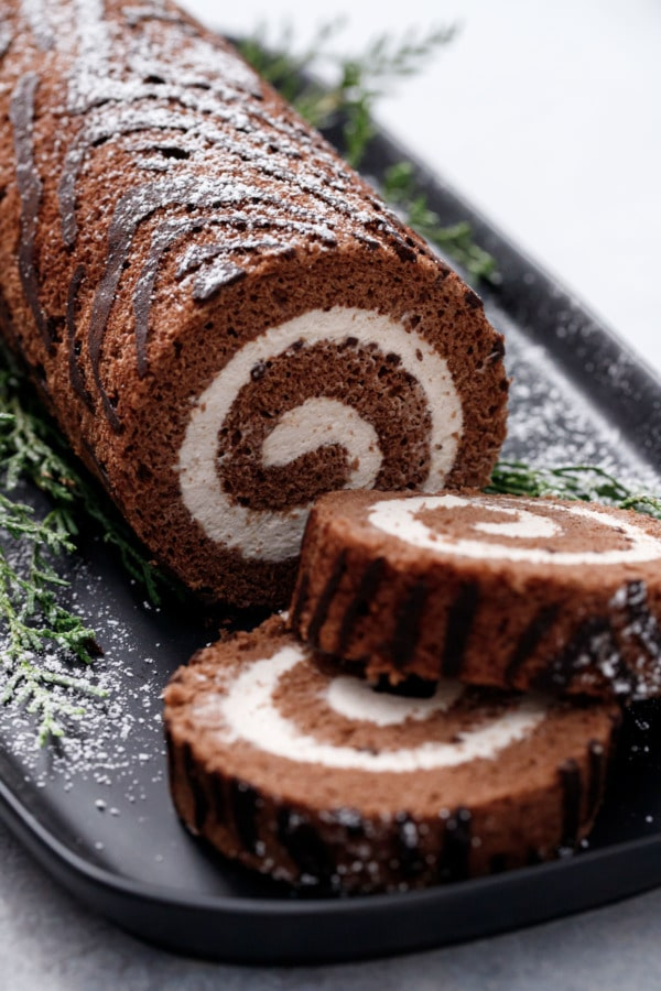 Closeup slices of Chocolate Chestnut Christmas Cake Roll, showing the perfect spiral of filling and the wood grain texture