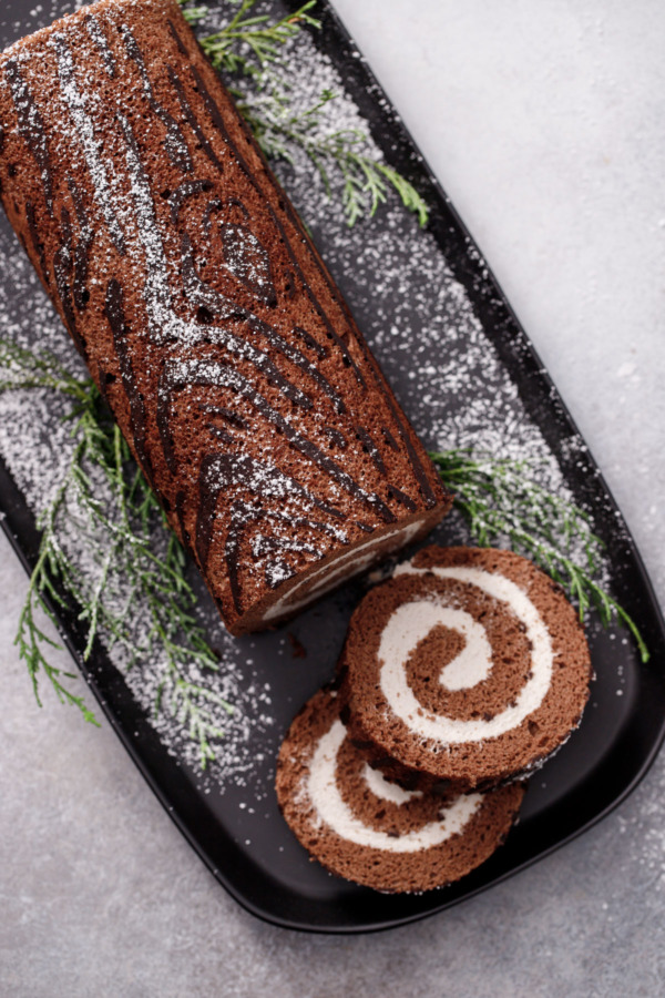 Overhead slices of Chocolate Chestnut Christmas Cake Roll, showing the perfect spiral of filling and the wood grain texture