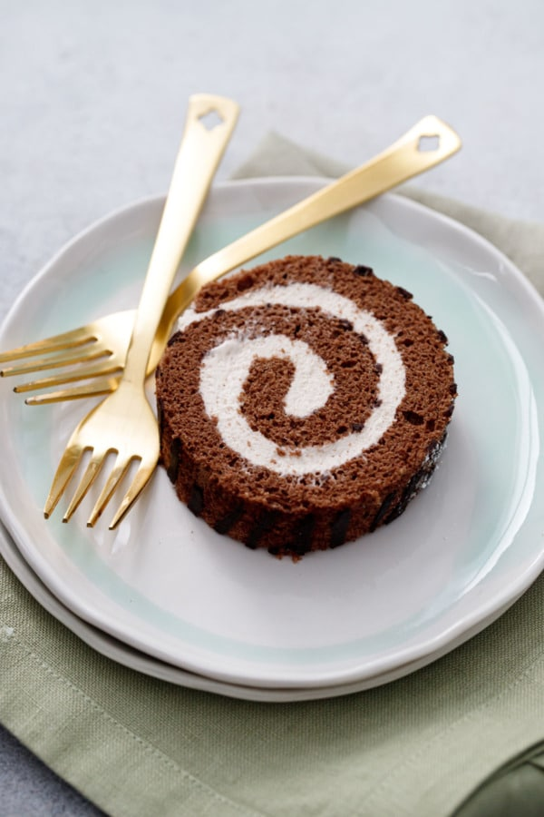 One spiral slice of Chocolate Chestnut Christmas Cake Roll on a ceramic plate with two gold forks