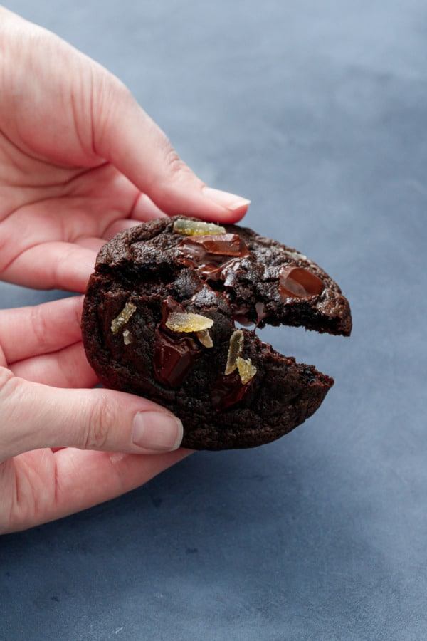 Hands breaking a Double Dark Chocolate Ginger Cookies in half, warm chocolate oozing