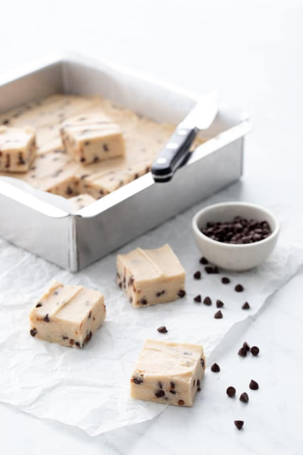 Pan of Chocolate Chip Cookie Dough Fudge, a few pieces cut out and a bowl of mini chocolate chips