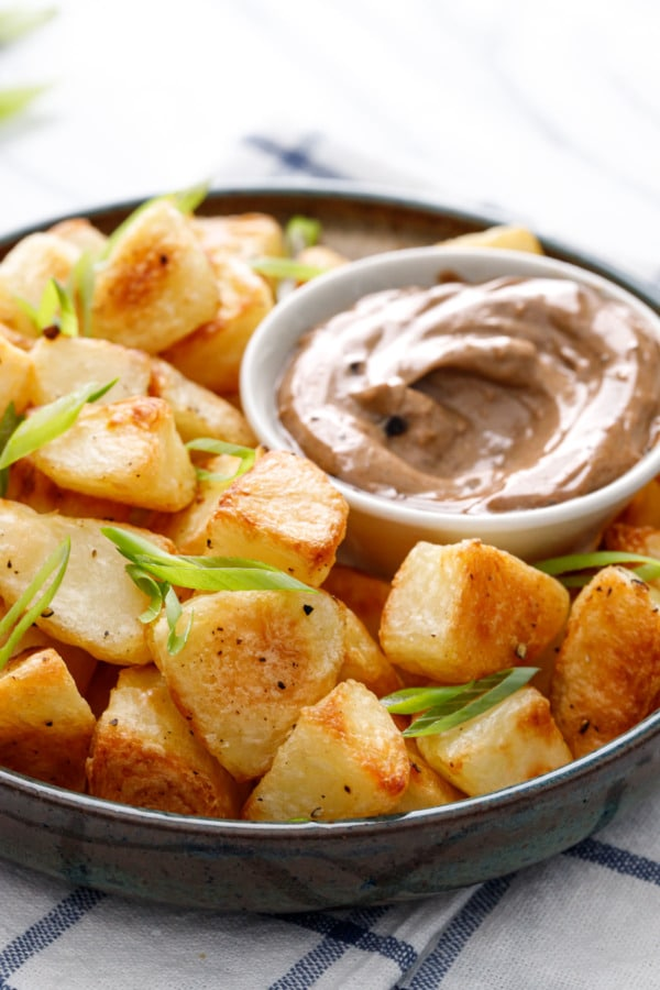 Shallow bowl filled with golden brown crispy potatoes, with a dish of black garlic aioli