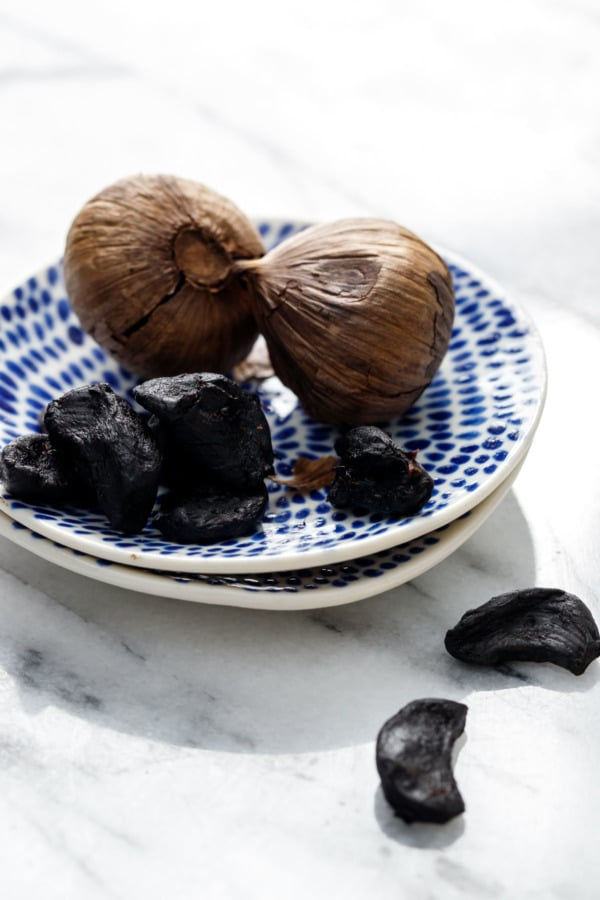 Cloves (both peeled and unpeeled) of black garlic on a blue painted ceramic dish.