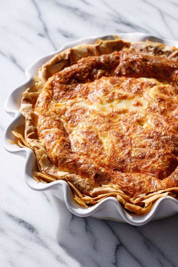 Deep dish quiche in a white ruffled pie dish, on a marble background in direct sunlight
