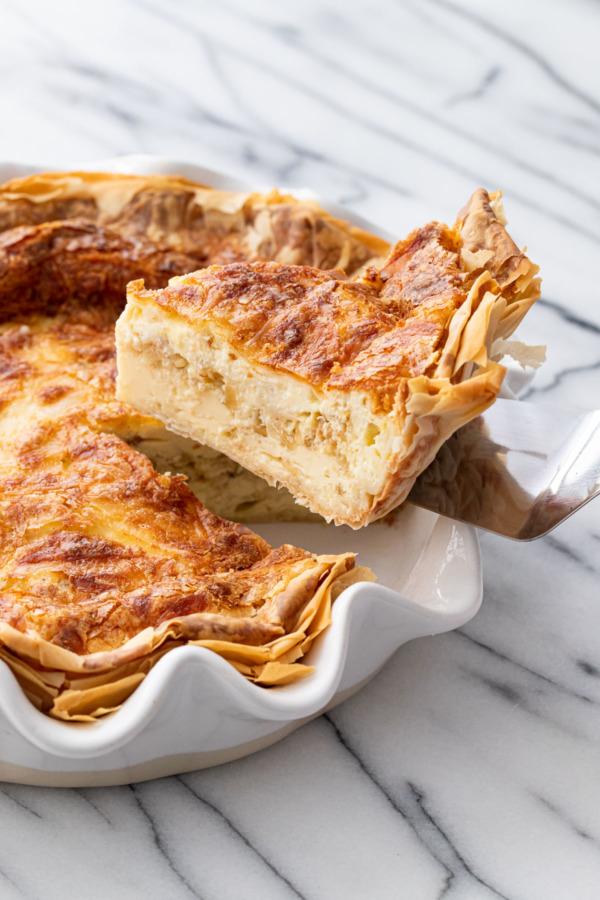 Вынимание ломтика пирога с сыром и карамелизованным луком из белой тарелки для пирога