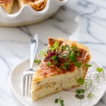 Slice of Cheese & Caramelized Onion Quiche topped with microgreens on a white ceramic plate