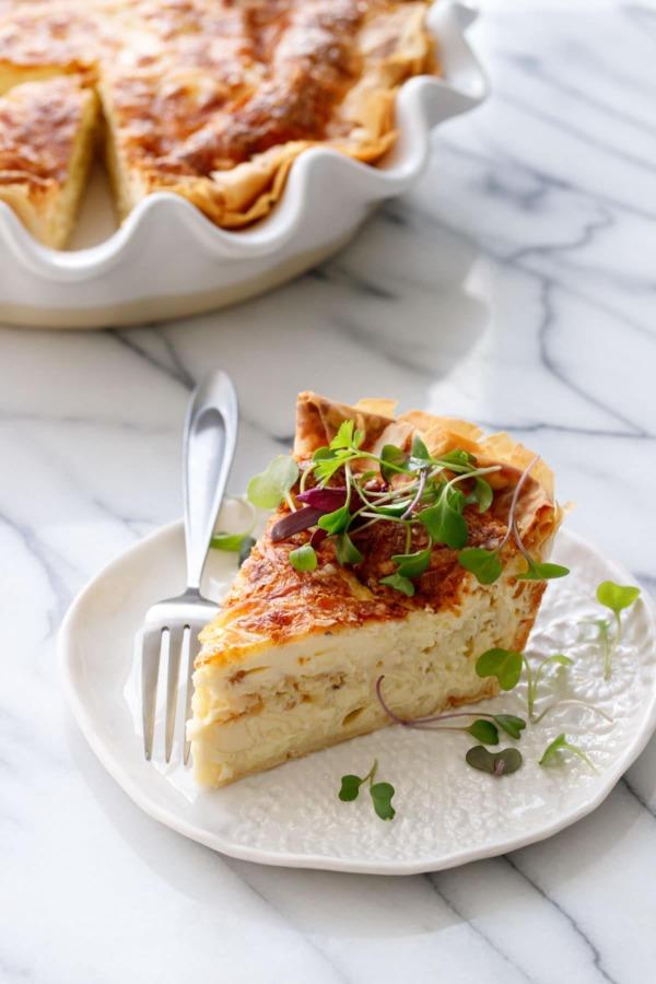 Кусок пирога с сыром и карамелизованным луком, посыпанный микрозеленью на белой керамической тарелке