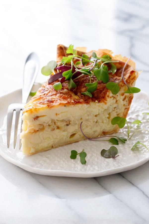 Ломтик пирога с сыром и карамелизированным луком, посыпанный микрозеленью, на белой керамической тарелке и вилке