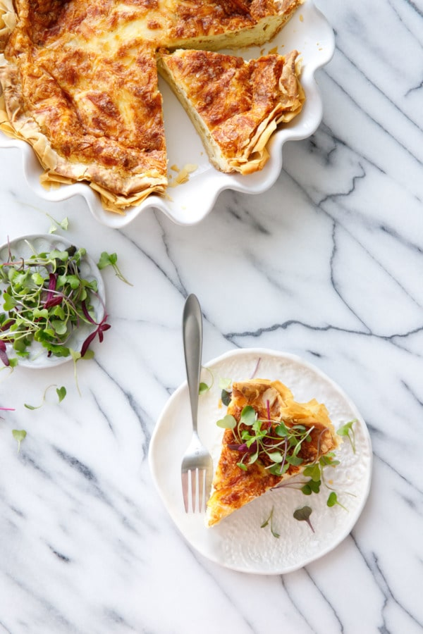 Overhead on marble, Quiche in white ruffled pie pan, plate with slice, and dish of microgreens