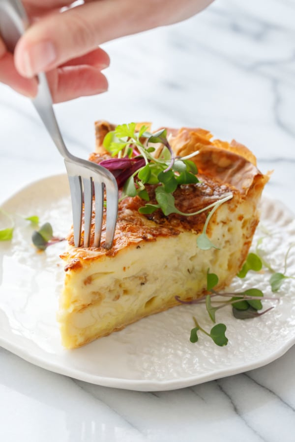 Fork in Slice of Cheese & Caramelized Onion Quiche topped with microgreens on a white ceramic plate and fork