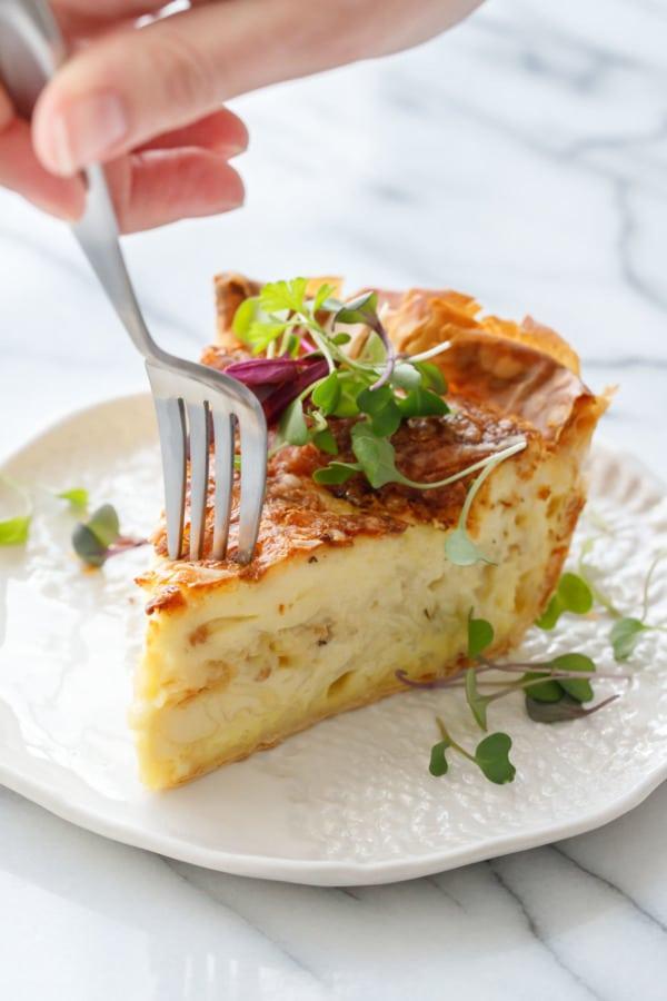 Вилка с кусочком сыра и карамелизированным луком, посыпанная микрозеленью, на белой керамической тарелке и вилке