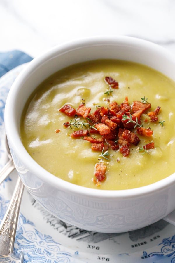 Closeup of cup of Split Pea Soup topped with crispy bacon bits and thyme