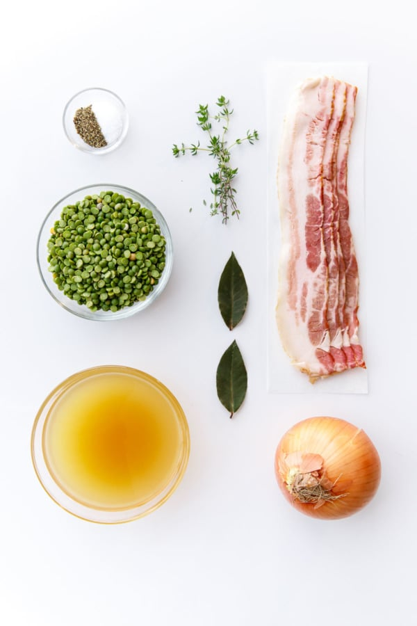 Overhead ingredients to make Split Pea Soup: Bacon, Onion, Split Peas, Bay Leaf, Thyme, Chicken Stock, Salt & Pepper