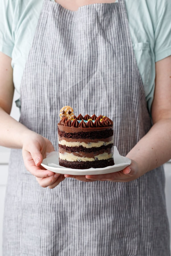 Person holding a plate with a mini naked layer cake to show the actual size/scale of the cake