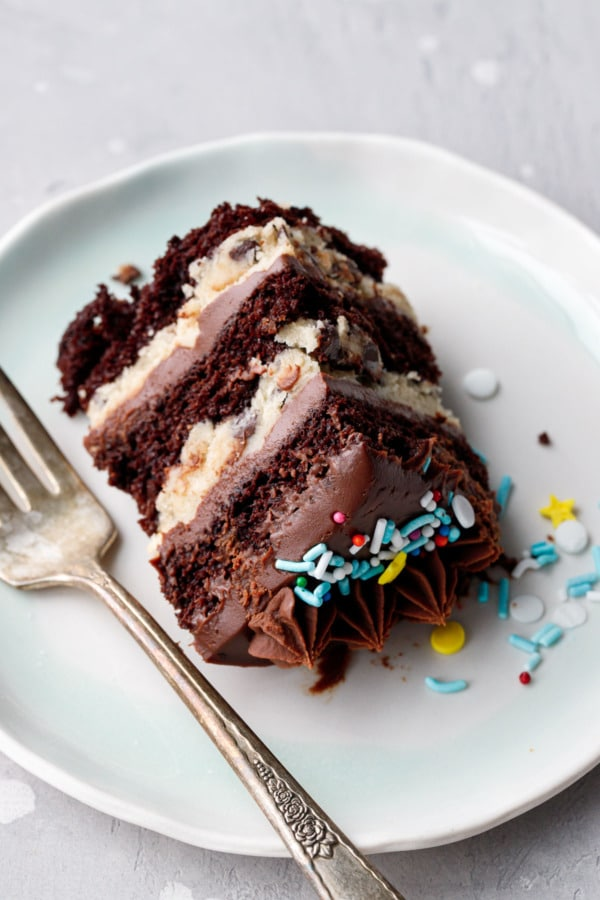 Slice of Mini Chocolate & Cookie Dough Naked Layer Cakes laying down on a ceramic plate with fork