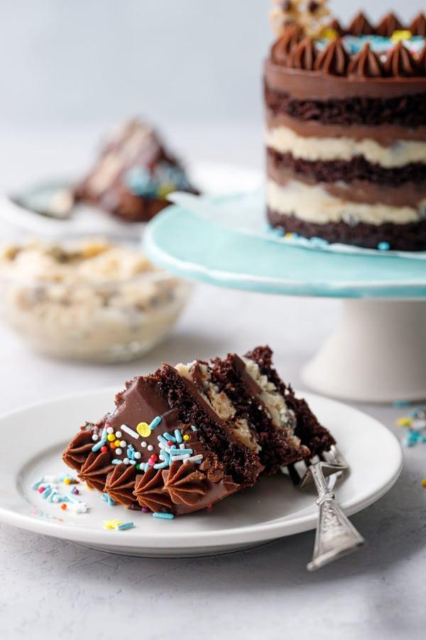 Кусочек мини-шоколадного теста с печеньем, голый слоеный пирог, полный торт на заднем плане