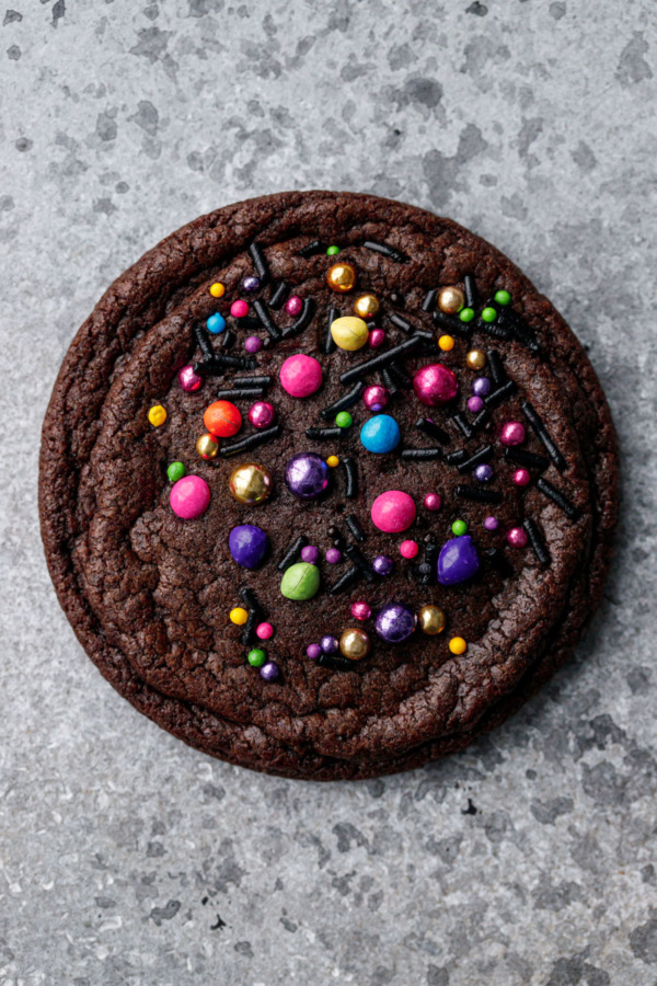 Single chocolate brownie cookie on a gray background with brightly colored rainbow and metallic sprinkles