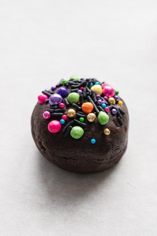 Closeup ball of brownie cookie dough topped with colorful rainbow sprinkles