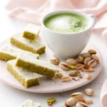 Fingers of Matcha Pistachio Shortbread on a ceramic plate with a mug of matcha and pistachios scattered around