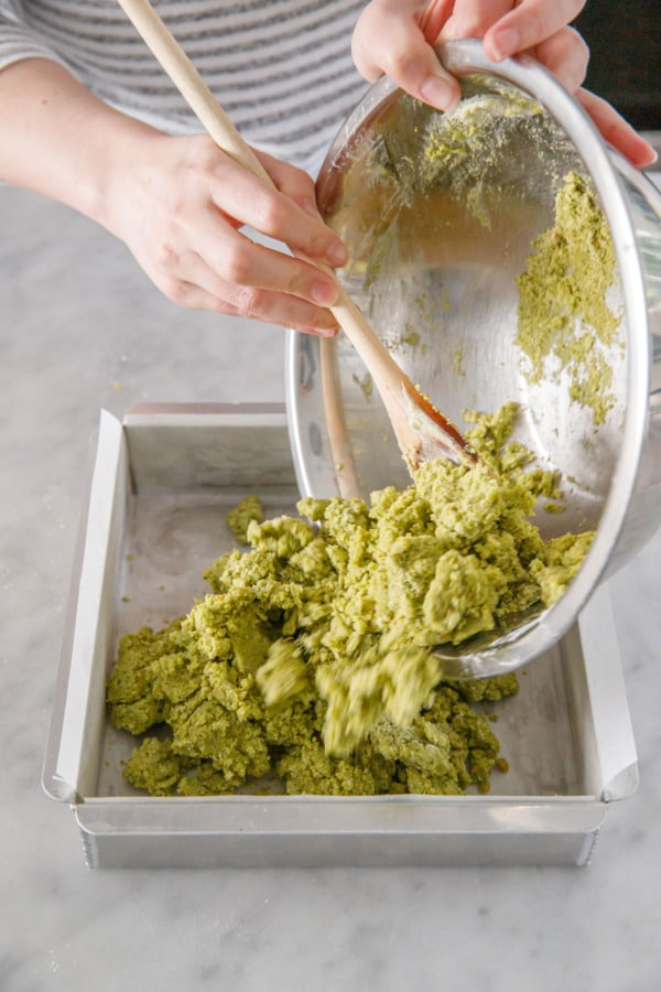 Dumping the green-tinted dough into a parchment-lined baking sheet